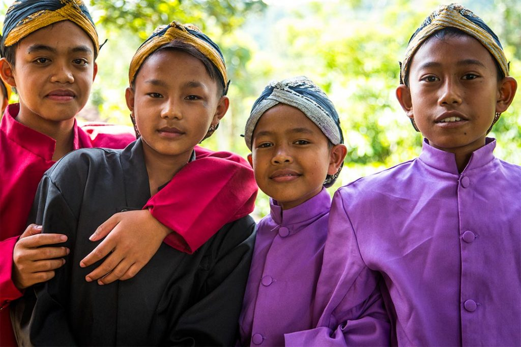 Four Indonesian boys stand together. They all wear ornate head scarves and silk, button up shirts.