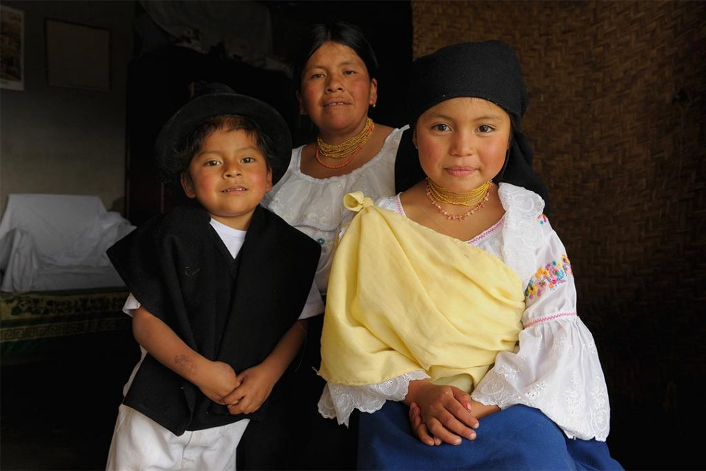 An Ecuadorian family of three sits and smiles at the camera. The daughter wears a black head scarf, an embroidered white blouse and a blue dress. Here mother is similarly attired. Her little brother where a traditional black hat as well as a black vest and white pants.