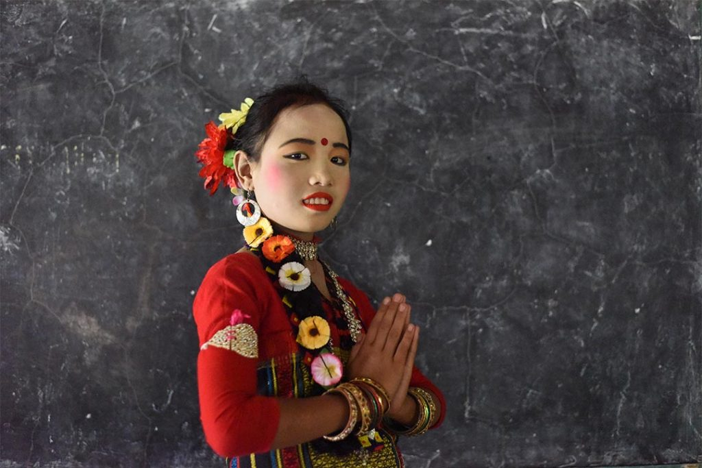 A young woman from Bangladesh where's traditional garb. She wears read lipstick, blush and eyeshadow and a red dot is painted on her forehead. She has flowers woven into here braided hair and bracelets cover her wrists. She wears an intricately embroidered red shirt.
