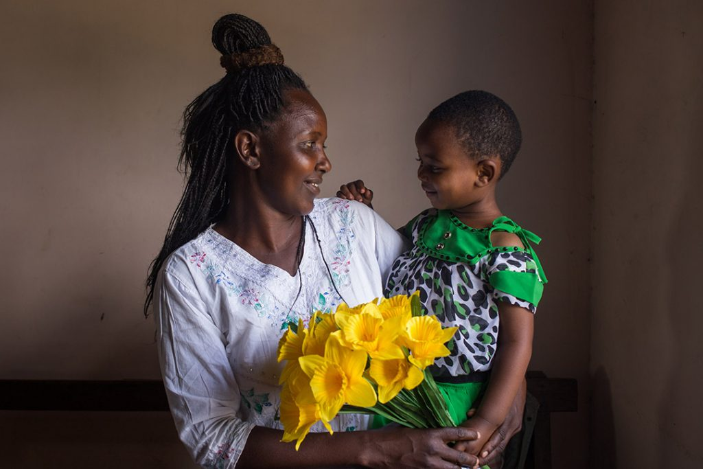 Winner, a Ugandan mother holds her infant son, Godnester and yellow bouquet of flowers. They are smiling at each other.