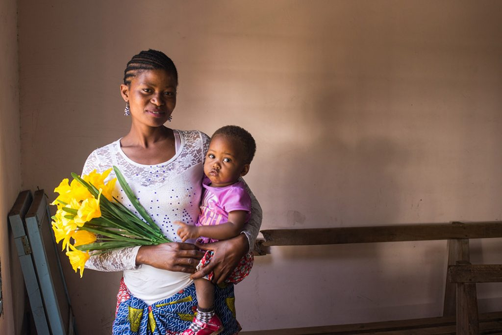 Neema, a Ugandan mother, stands inside a building holding her daughter, Tumaina and bouquet of yellow flowers.
