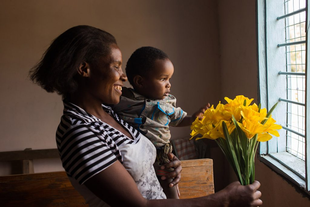 Selena, a Ugandan mother, holds her infant son Jemaal and bouquet of yellow flowers. They both look out a window.