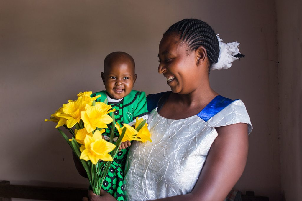 Esta, a Ugandan mother, holds here infant daughter, Zena and bouquet of yellow flowers. Both smile.