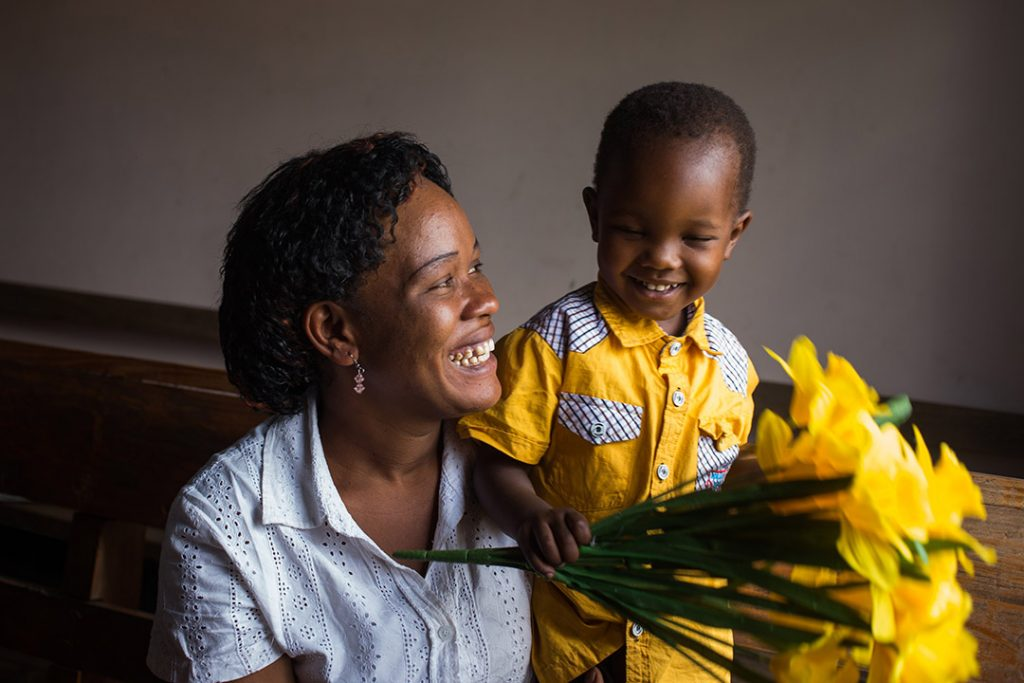 Lucy, a Ugandan mother holds her infant son, Crispin and yellow bouquet of flowers. They are smiling at eachother.