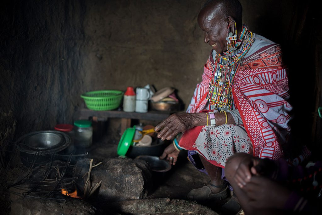 Nasinde sits in her kitchen. It has a dirt floor, dirt walls and various utensils stacked on small shelf