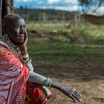 Nasinde, a 75 year old from Kenya, sits in front of her home.