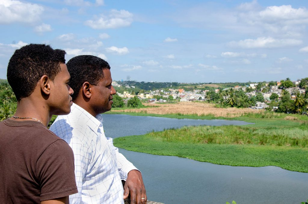 Pablo, a pastor and Compassion centre director, stands with his son Vladimir. They look out over a river near their church.
