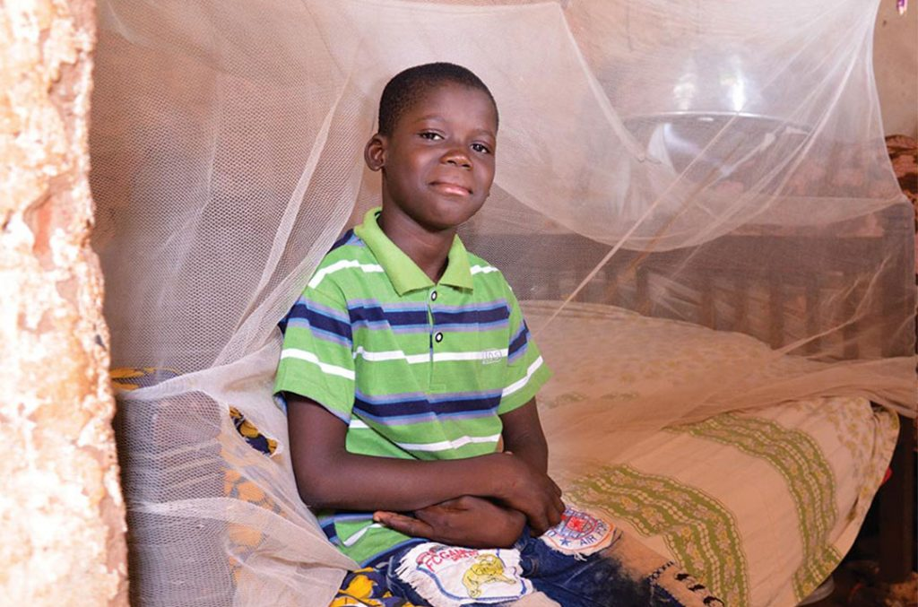 A boy sits on his bed. A mosquito net is draped behind him.