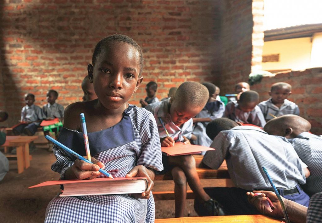 A child sits on a bench in brick classroom. She writes with a pencil, using her textbook as a hard surface to write on.