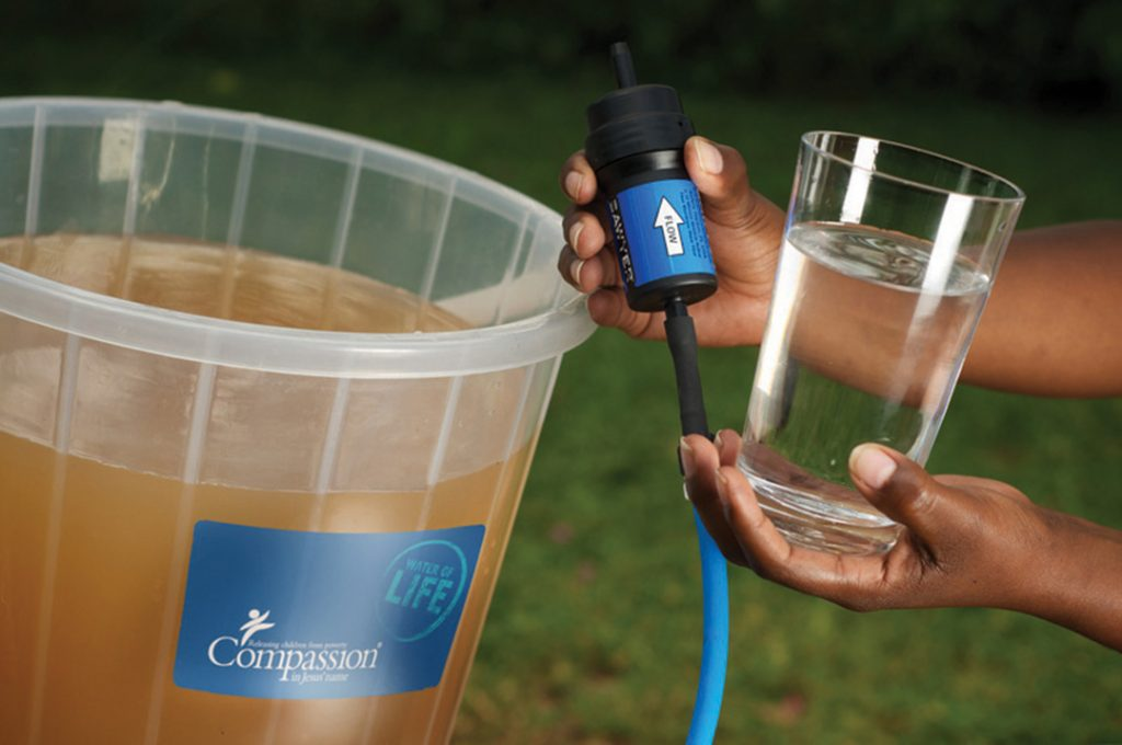 A water filter held up between dirty water and a glass of clean, filtered water.
