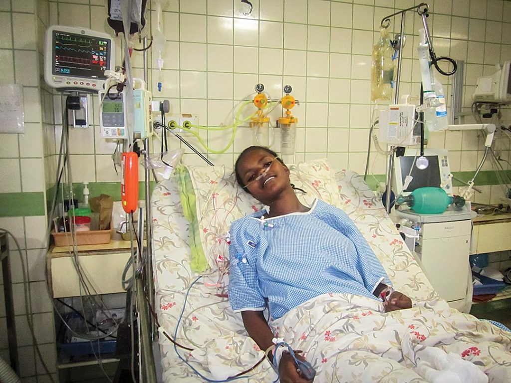 A teenage girl sits in hospital bed. Recovering from surgery.