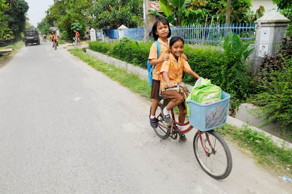 Two girls ride down the street on one bike. They both wear peach coloured shirts with brown dresses.