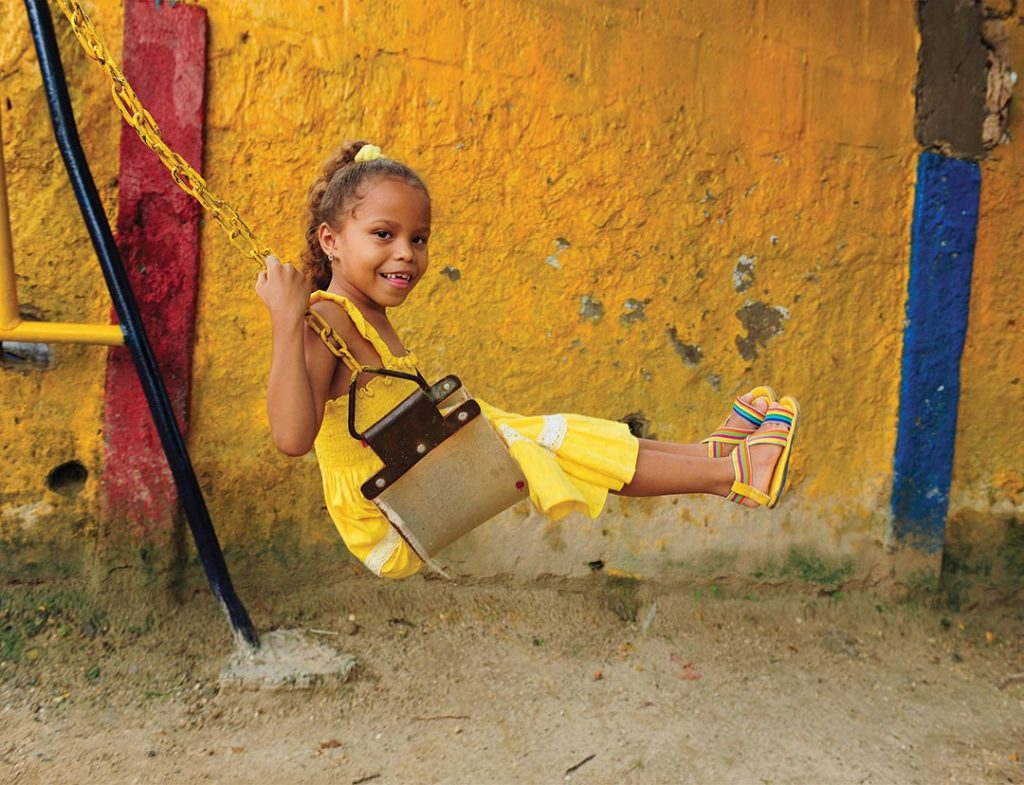 A young girl in a yellow dress, swings on a swing-set and smiles.