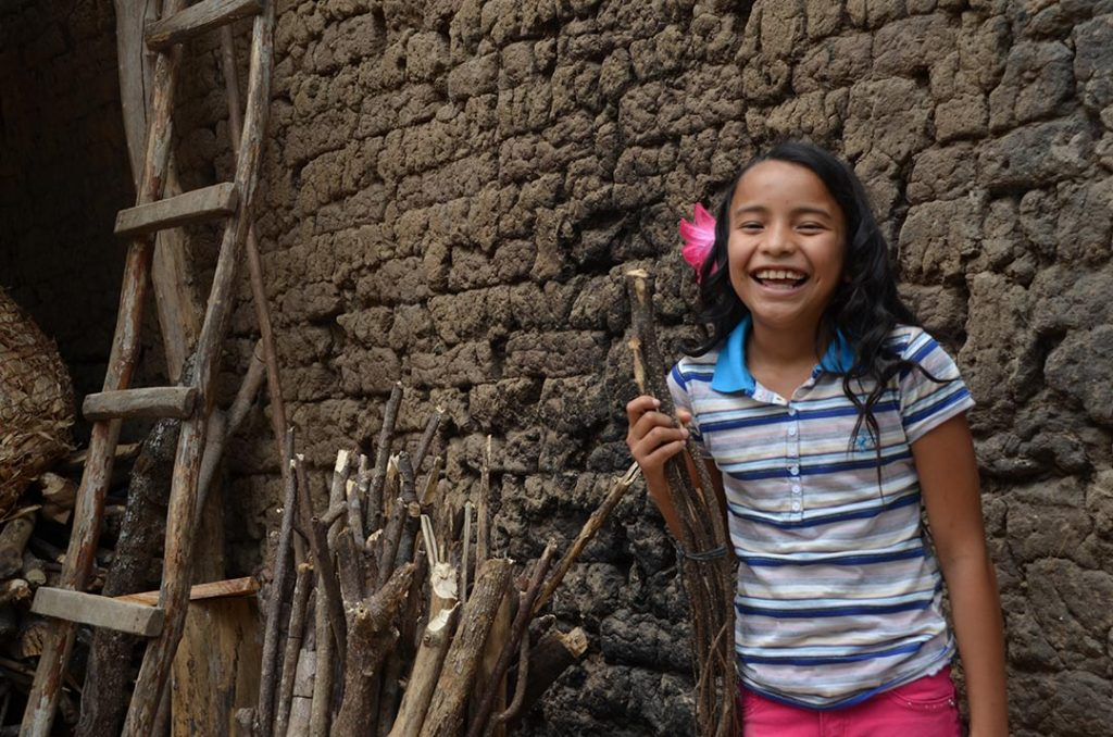 A girl laughs as she stands beside a pile of sticks, leaned against a wall.