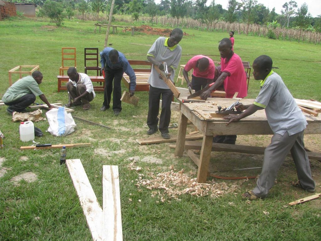 Men work with saws and other tools as they build chairs and tables