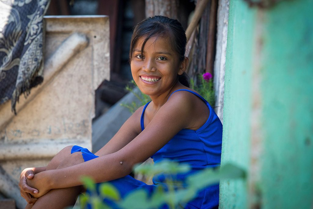A girl a blue dress sits outside of a blue doorway and smiles.