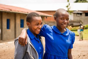 Two young girls, teens, teenagers stand outside the project with their arms around each other, hugging as they smile for the camera. They are both wearing the blue dress project uniform.