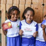 Three girls stand against a wooden fence holding up Christmas cards.