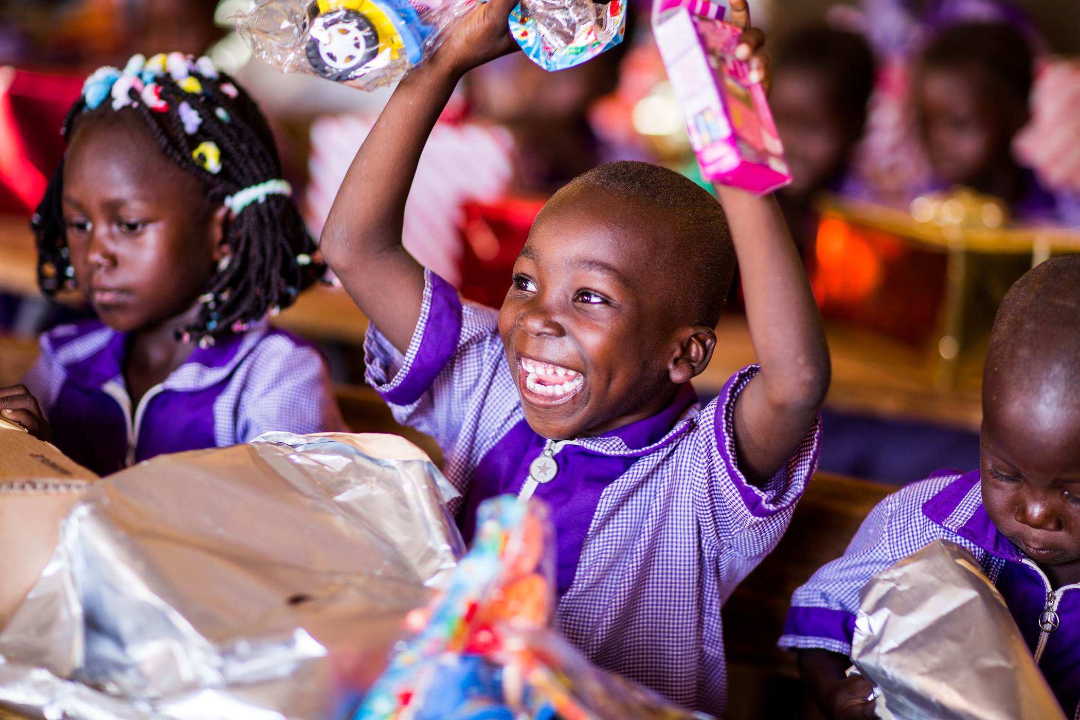 I little boy in Burkina Faso sits in class, opening his christmas presents. He looks very excited, smiling as he holds his new toys above his head.