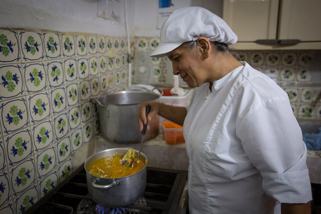 A compassion centre worker checks on the soup she's making for a special, Christmas meal. She stands in tiled kitchen and stirs the soup with her ladle.