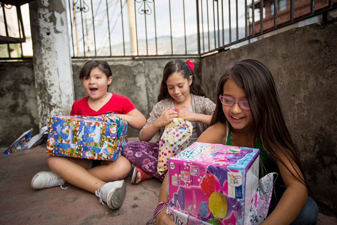 Three girls sit next to the wall of their Compassion centre and open gifts. They look very excited.