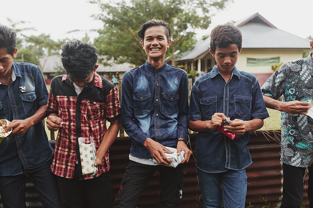 Indonesian, teenage boys stand together opening presents. One smiles as he looks a the camera.