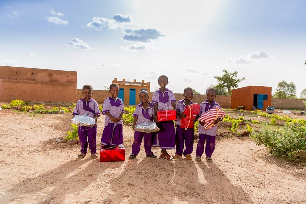 Six children from Burkina Faso stand in front of their Compassion centre. It has brown walls and vibrant, blue doors. They were ornate, purple school uniforms and hold Christmas presents