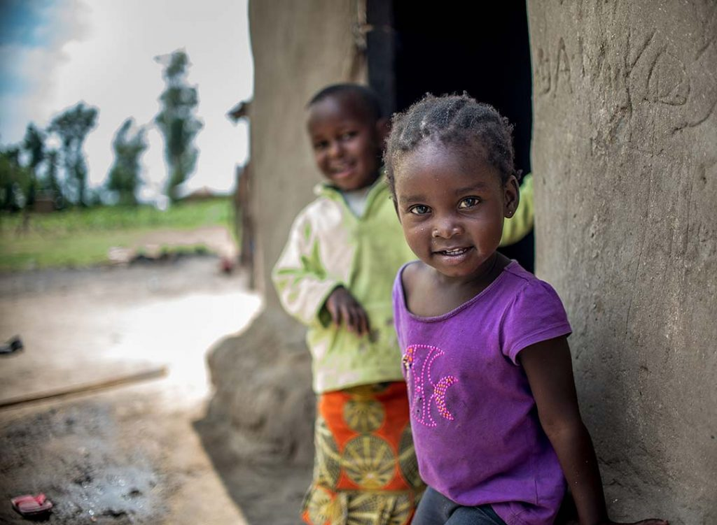 Two little girls stand outside the door of their mud hut.