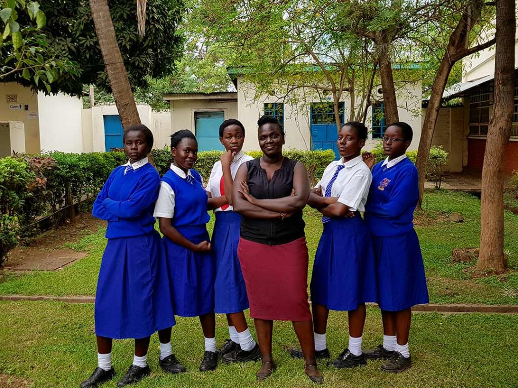 Six young women stand in the yard of their school. Five of them where blue and white school uniforms. One wears a black blouse and red dress.