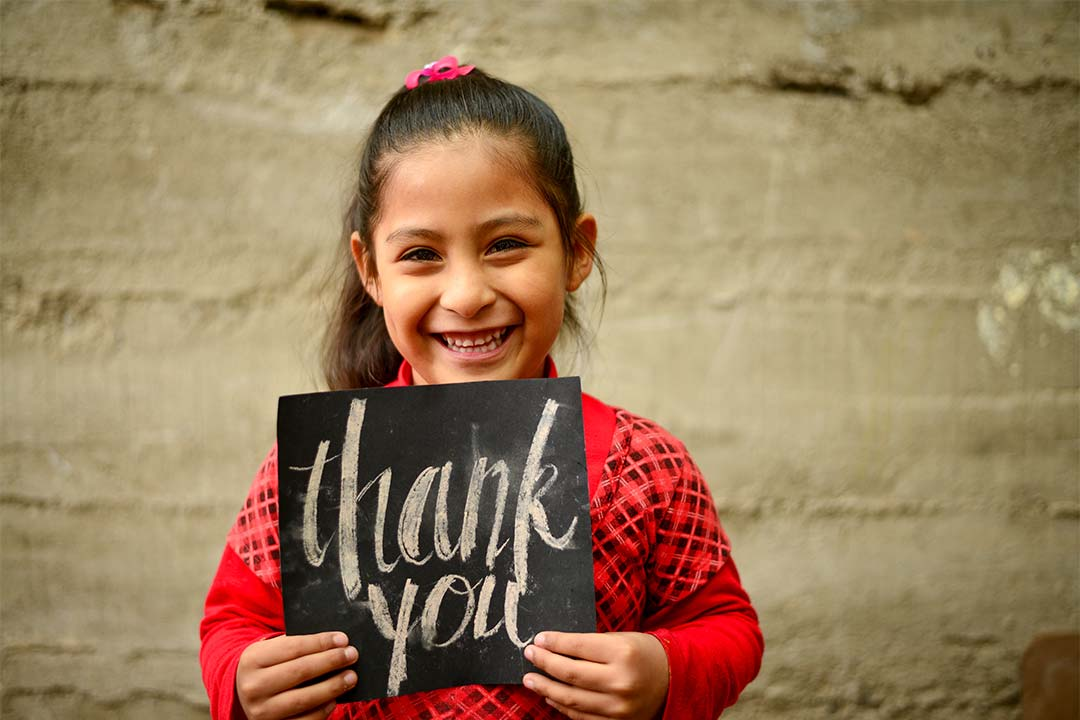 Paola, a girl from Peru, smiles at the camera holding a black sign that says, Thank You. She has brown hair and wears a plaid, red shirt.