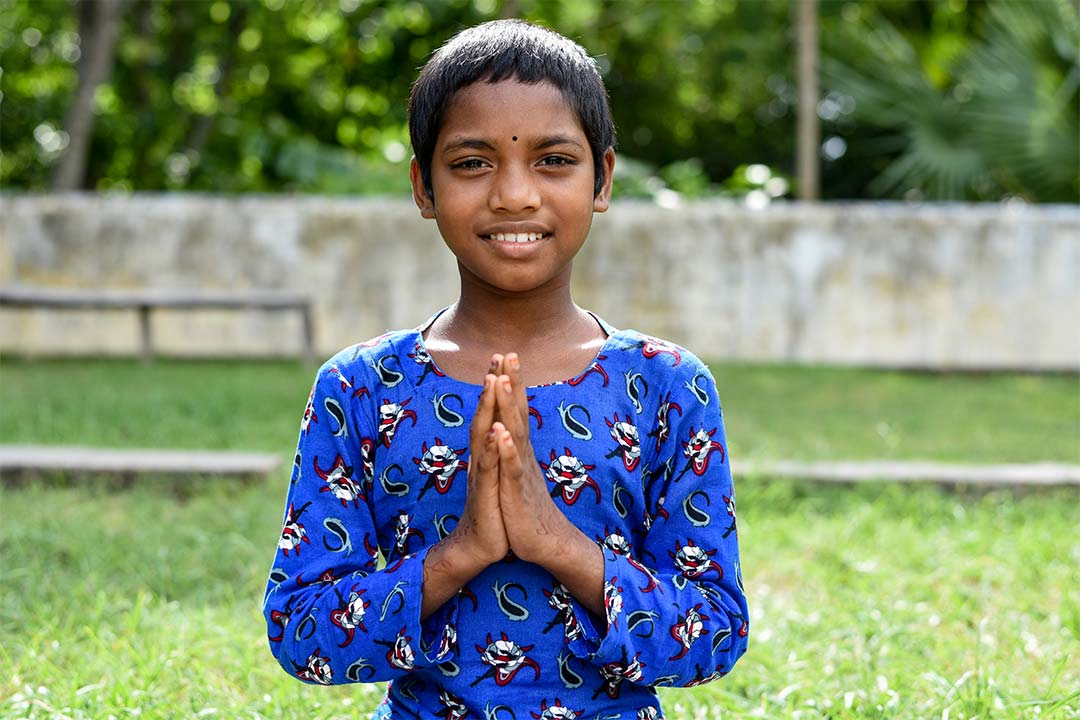 Puja, a girl from Bangladesh, stands in front of a green field smiling at the camera. She has, short, black hair and wears an ornate blue shirt.