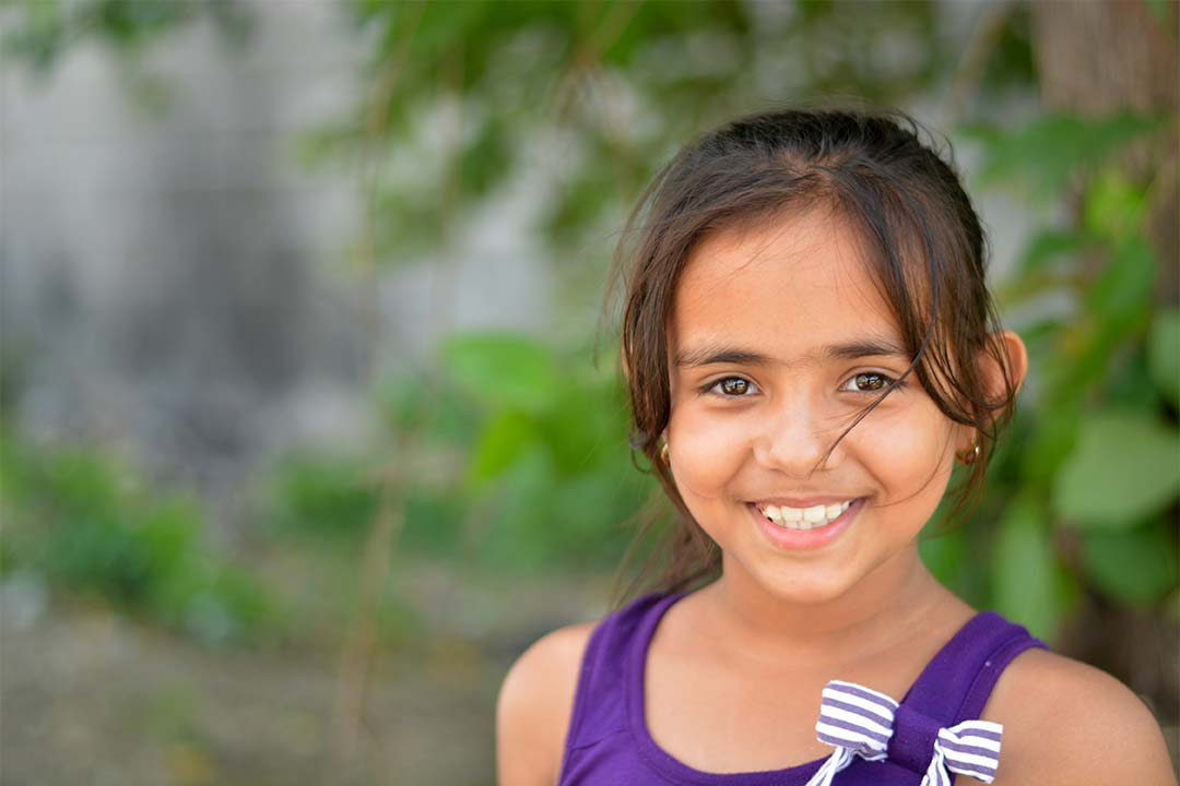 Ruth, a girl from honduras, smiles at the camera. She has brown hair and wears a shirt with a ribbon on it.