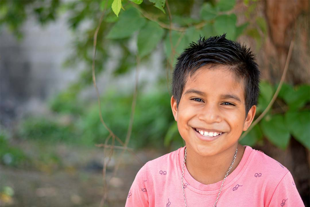 Hector, a boy from Honduras, smiles at the camera. He has black hair and wears a pink t-shirt with a pattern of eye glasses on it.