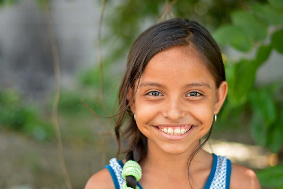 Cinthia, a girl from Honduras, smiles at the camera. She has brown, braded hair and wears a blue and white tank top.