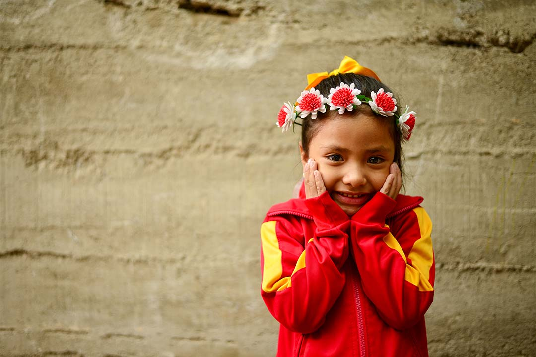 Bella, a girl from honduras, smiles at the camera with her hands on her cheeks. She has brown hair and wears a red shirt and head band made out of flowers.