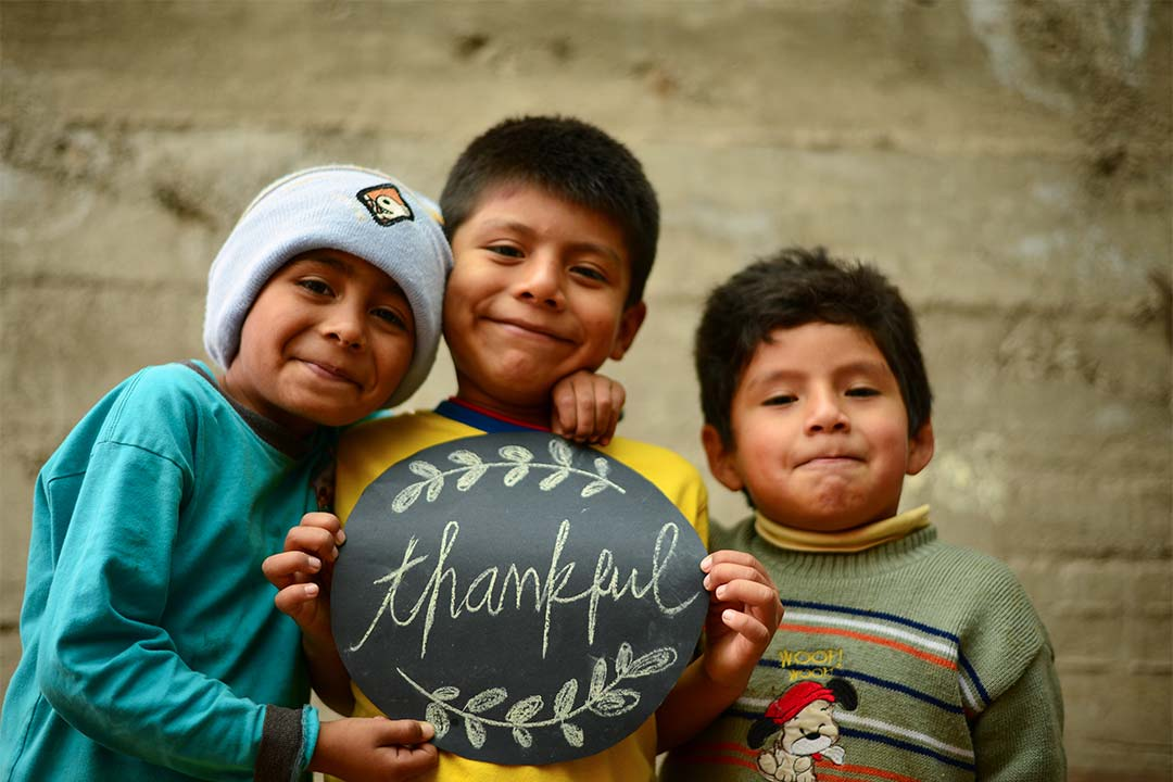 Amir, a boy from Peru, stands with two other boys and smiles at the camera. He wears a blue toque and blue shirt. His friend holds up a sign that says, Thankful.
