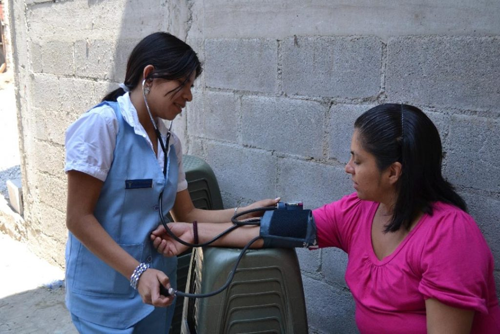 A young nurse in a nursing uniform, takes someone's blood pressure as they sit out on the street.