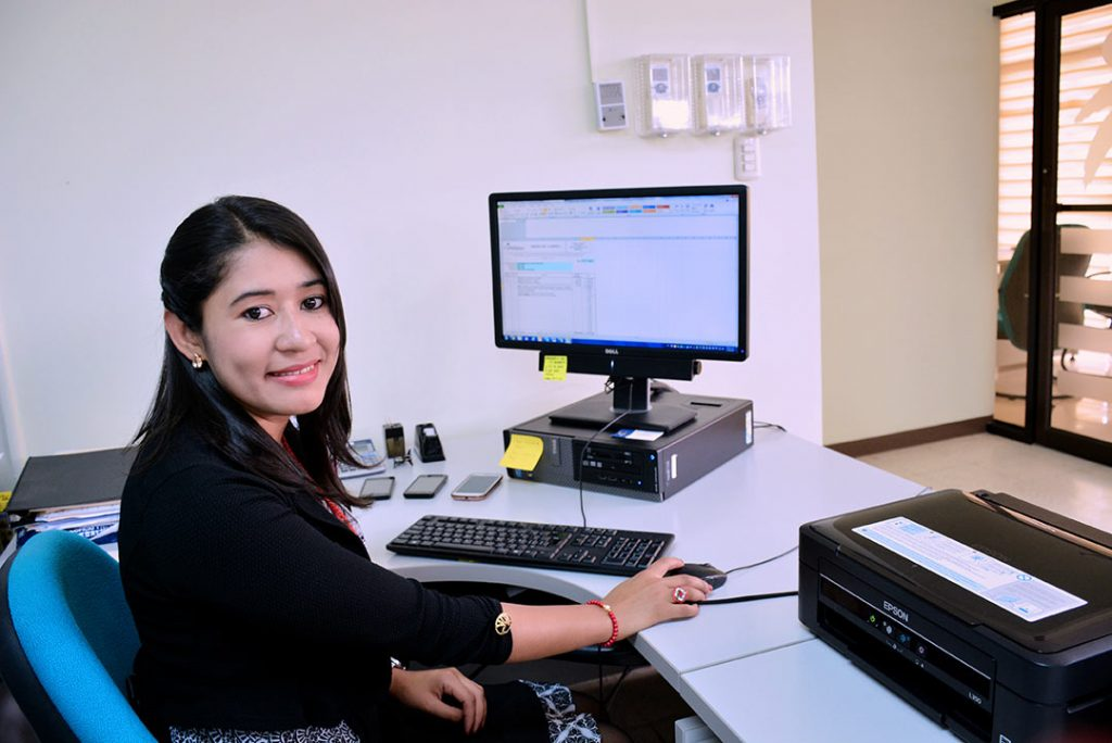 A young woman sits in front of a computer in an office.