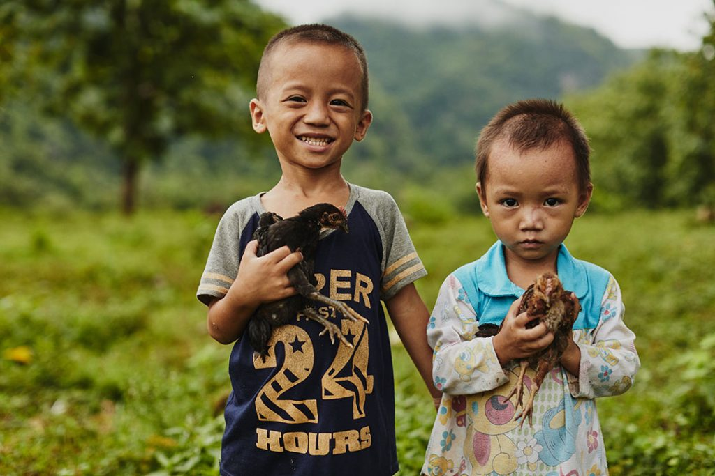 Two young Thai brothers stand together holding chickens