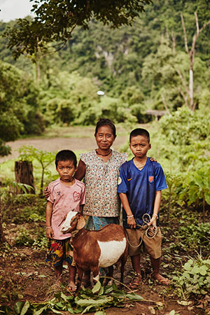Two young Thai boys stand with their aunt. Their goat stands in front of them.