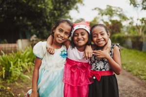Three Indonesian girls stand together and smile with their arms around each other's shoulders. The middle girl is wearing a red hat.
