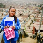 A girl stands at the top of a set of stairs overlooking city. She's holding pink bag full of paper and letters.
