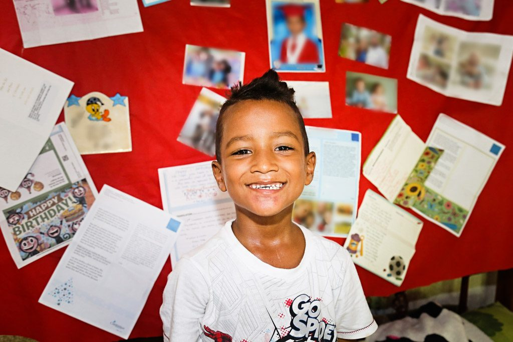 A boy sits infront of a red boad covered in pictures and letters. He smiles at the camera.