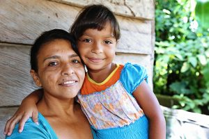 A Columbian mother sits with her daughter on her lap and smiles at the camera.