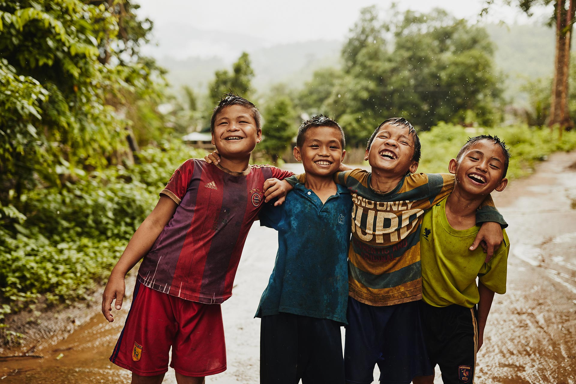Four Thai thai boys stand in the rain and laugh together.