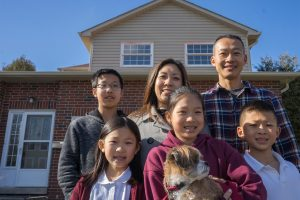 A family stand in front of their new house.