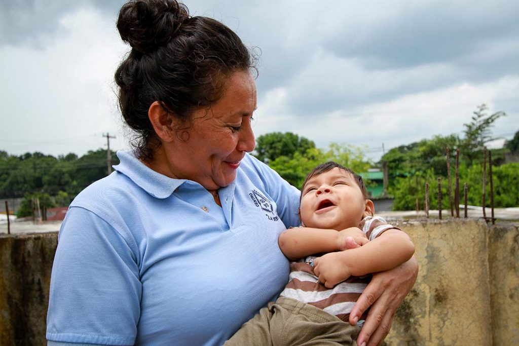 A compassion worker holds a baby boy in her hands and smiles at him.