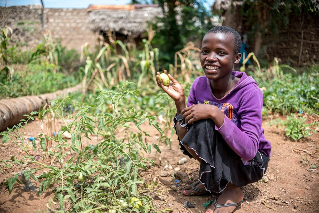 A girl stands in her family garden and holds up some fresh produce.
