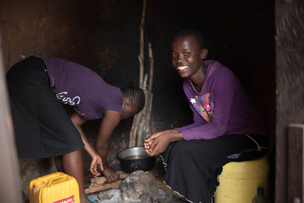 A girl sits inside her families hut as someone cooks over a fire.