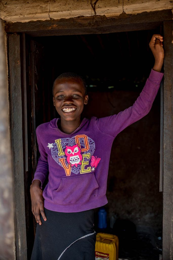 A girl wearing a purple shirt, stands in a doorway and smiles.